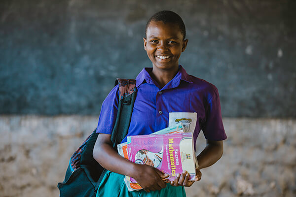 student with books and bookbag