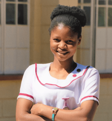 Margret-stands-in-front-of-a-health-clinic-in-Malawi