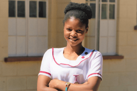 Margaret-standing-in-front-of-a-health-clinic-in-Malawi
