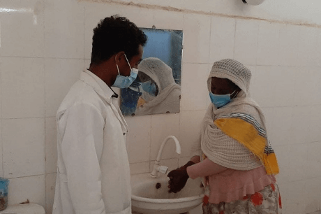 Two Ethiopians both with masks on with one washing their hands