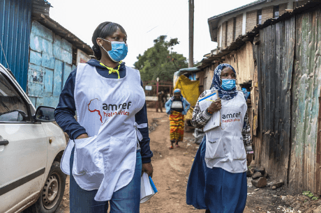 Two community health workers with masks and amref merchandise on