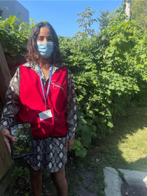Female wearing mask and amref uniform who works door to door